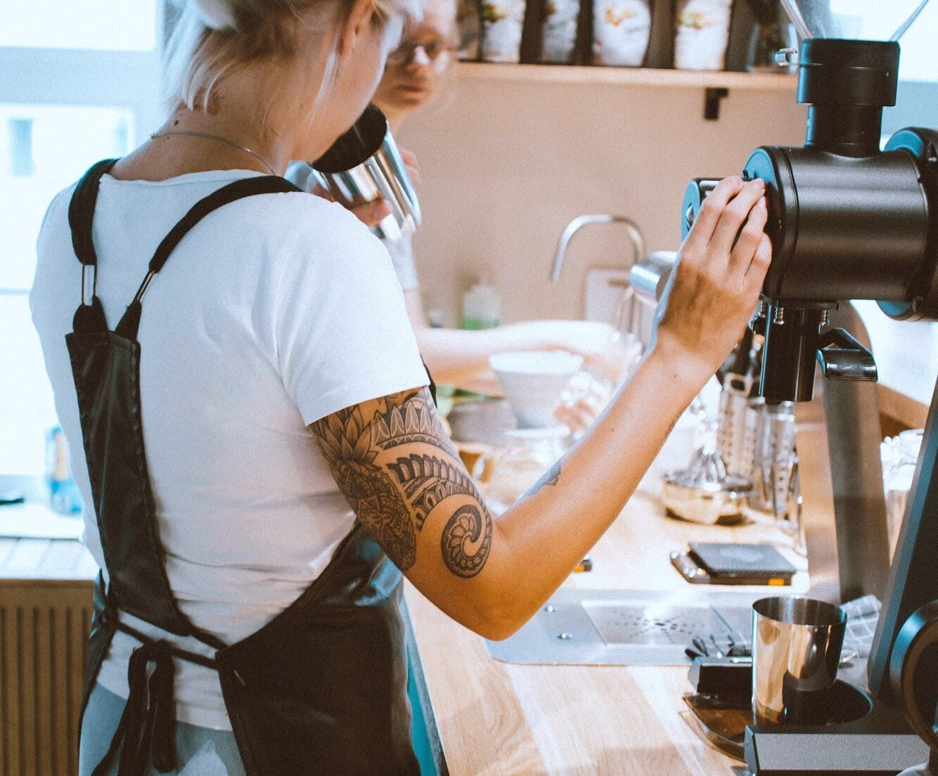 A barista is preparing a coffee for a customer