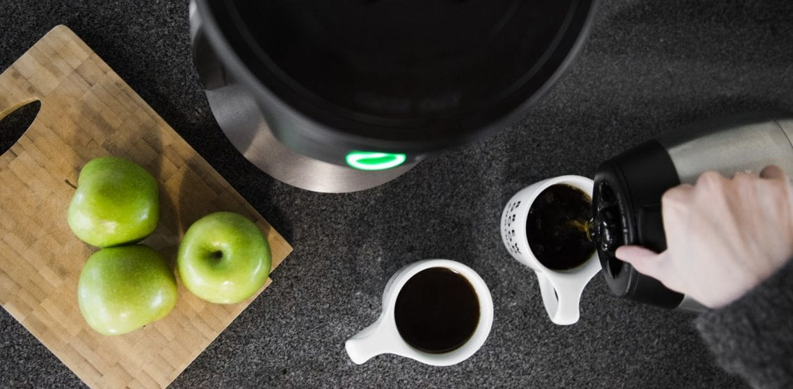 Filter coffee made with a Bunn served into two white cups on a black surface. Woode tray with green apples
