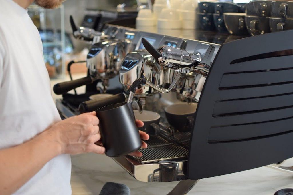 Barista crema leche en una máquina espresso