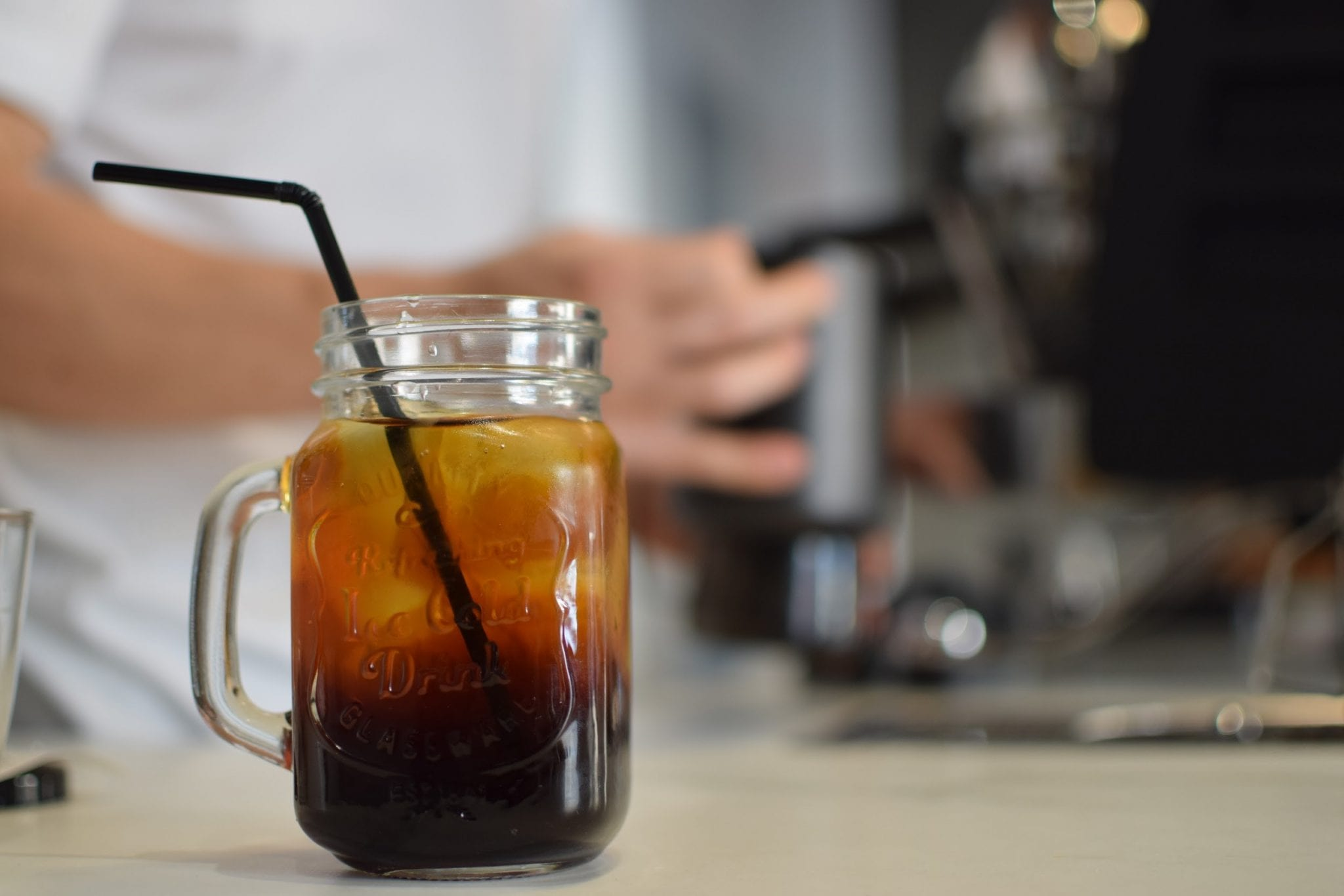 A glass of cold brew coffee with straw.