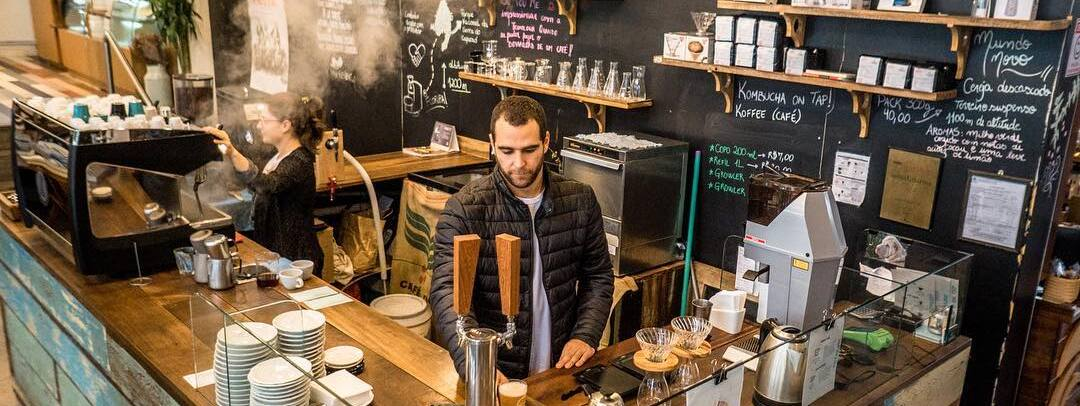Barista behind the bar making espressos