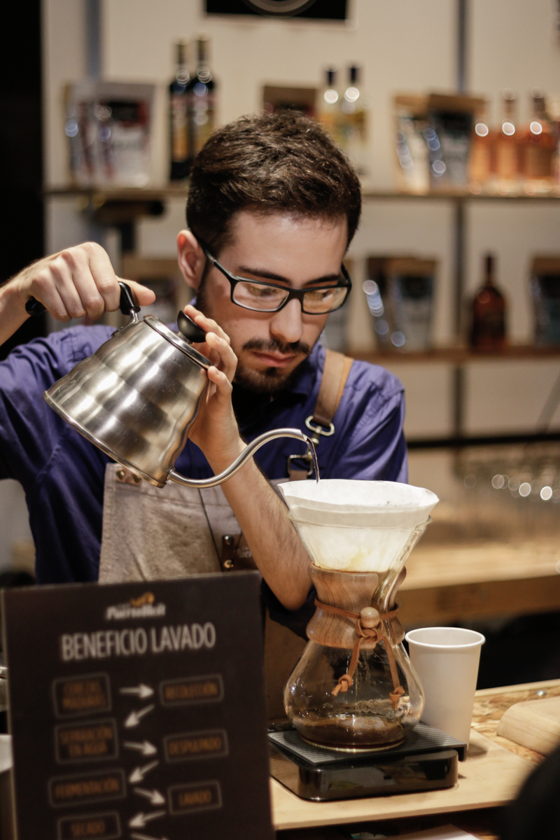 A barista pours water into a Chemex pour over device.