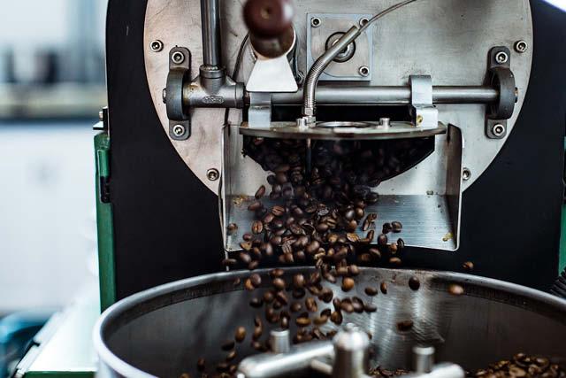 O café é derramado no resfriador depois de torrado.