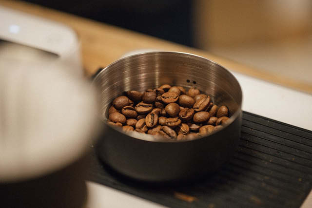 roasted coffee beans being weighed