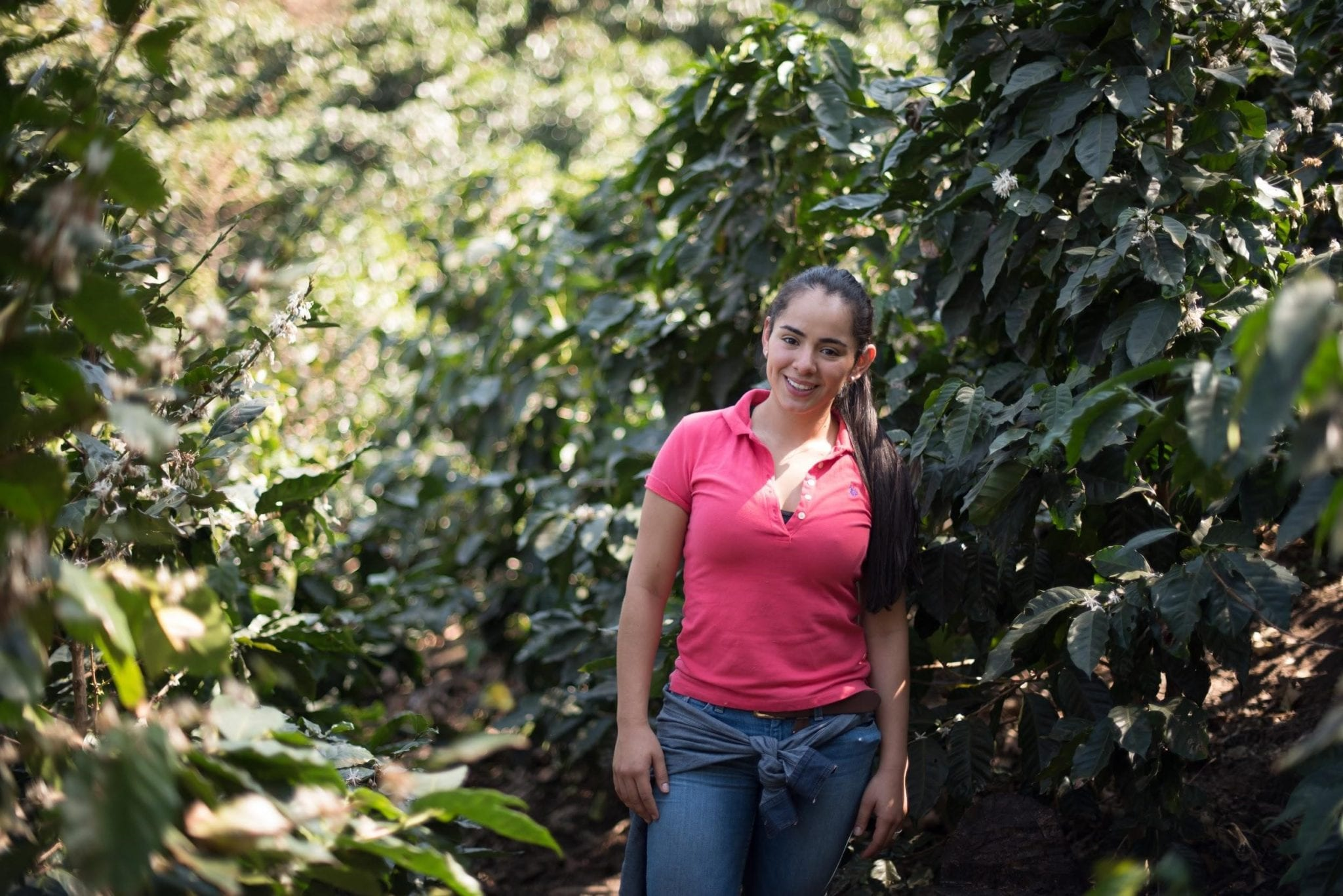 female coffee producer among the coffee trees on her farm