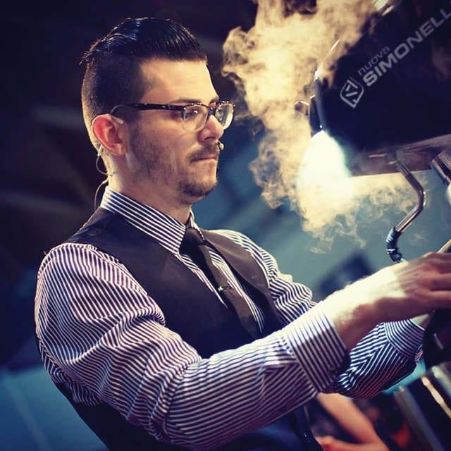 barista steams milk with Nuova Simonelli machine