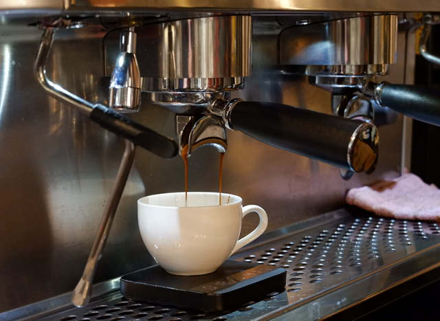 brewing shot of espresso into cup