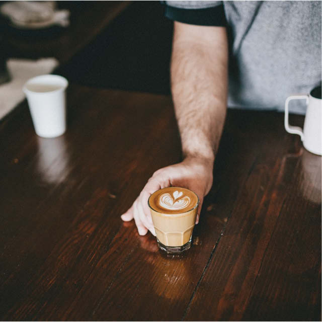 barista serving flat white