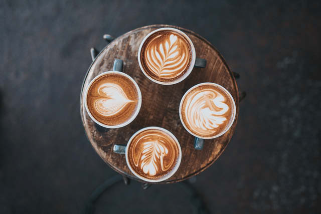 4 flat whites with different latte art designs