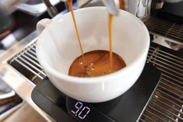 Shot of espresso pouring into cup