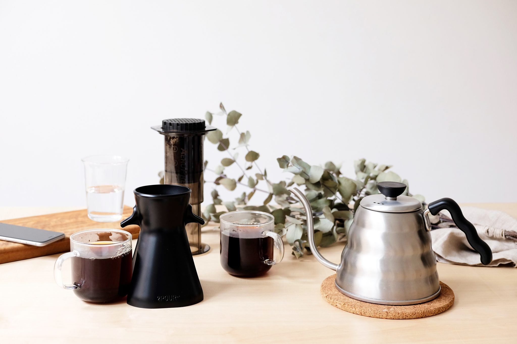 Wooden table with coffee equipment and cups of coffee
