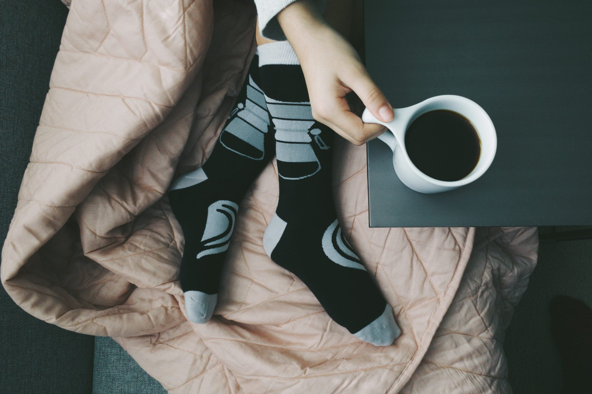 Coffee-themed socks and hand holding a cup of coffee.