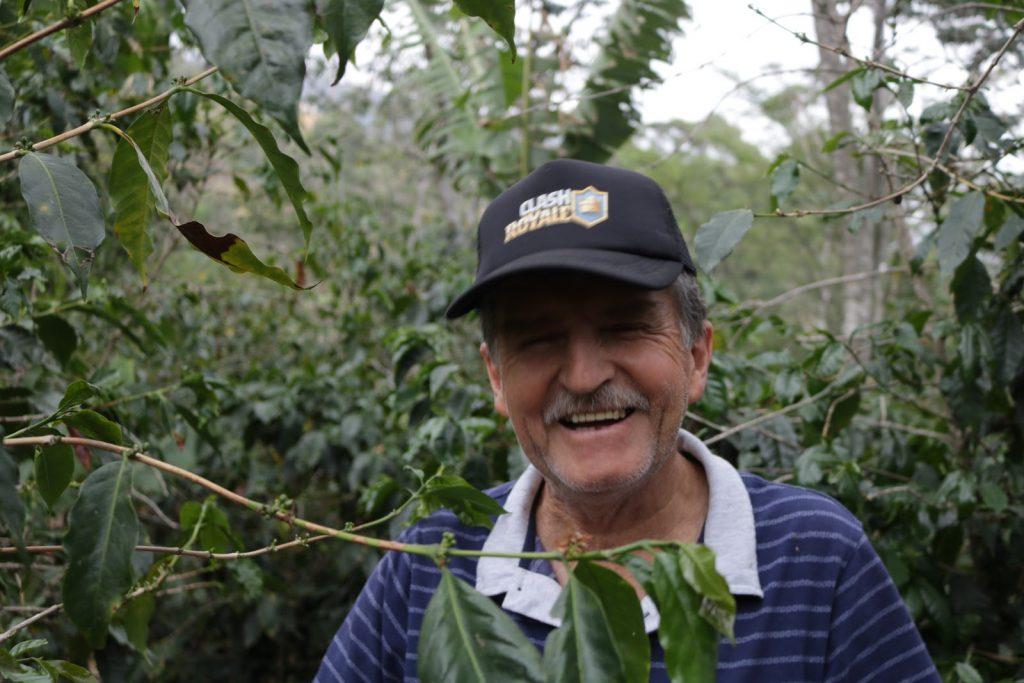 productor de cafe sonrie en su finca cafetera