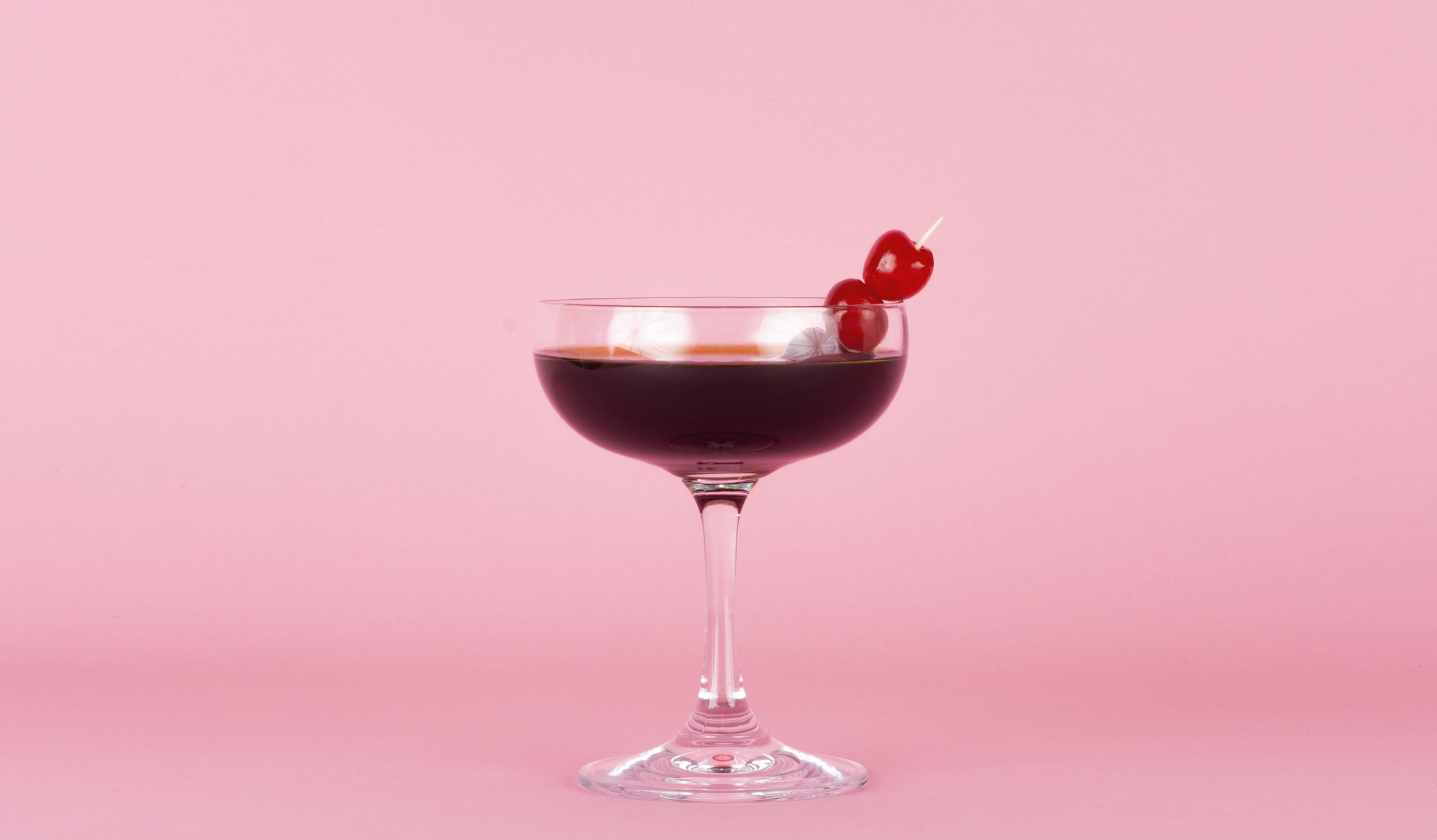 Glass of a Martini drink made with coffee in a pink background