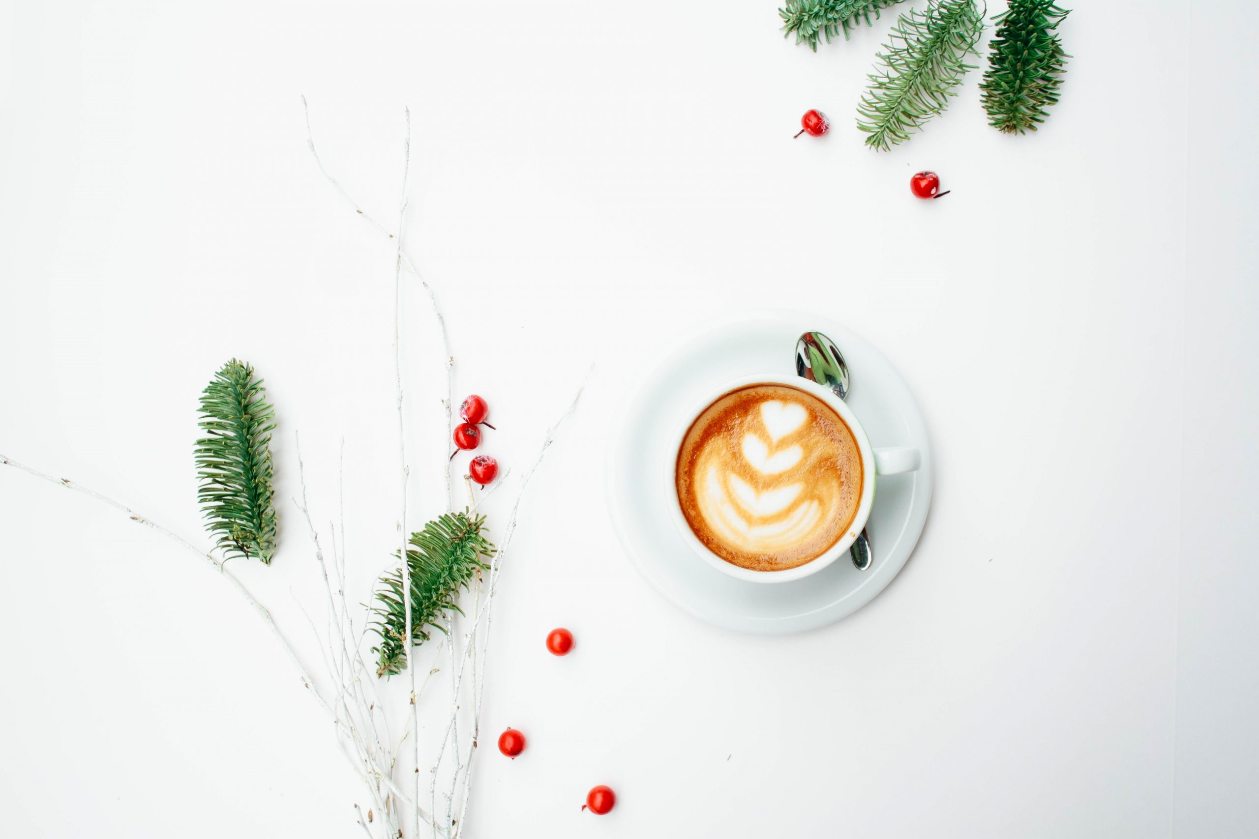 Cappuccino in a white cup on a marbeled surface with christmas decorations