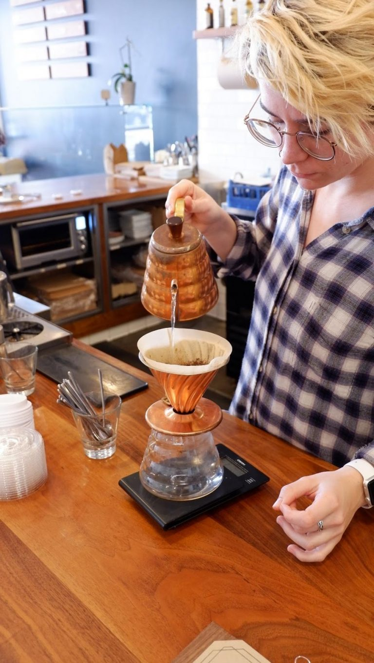 barista brewing coffee in pour over method