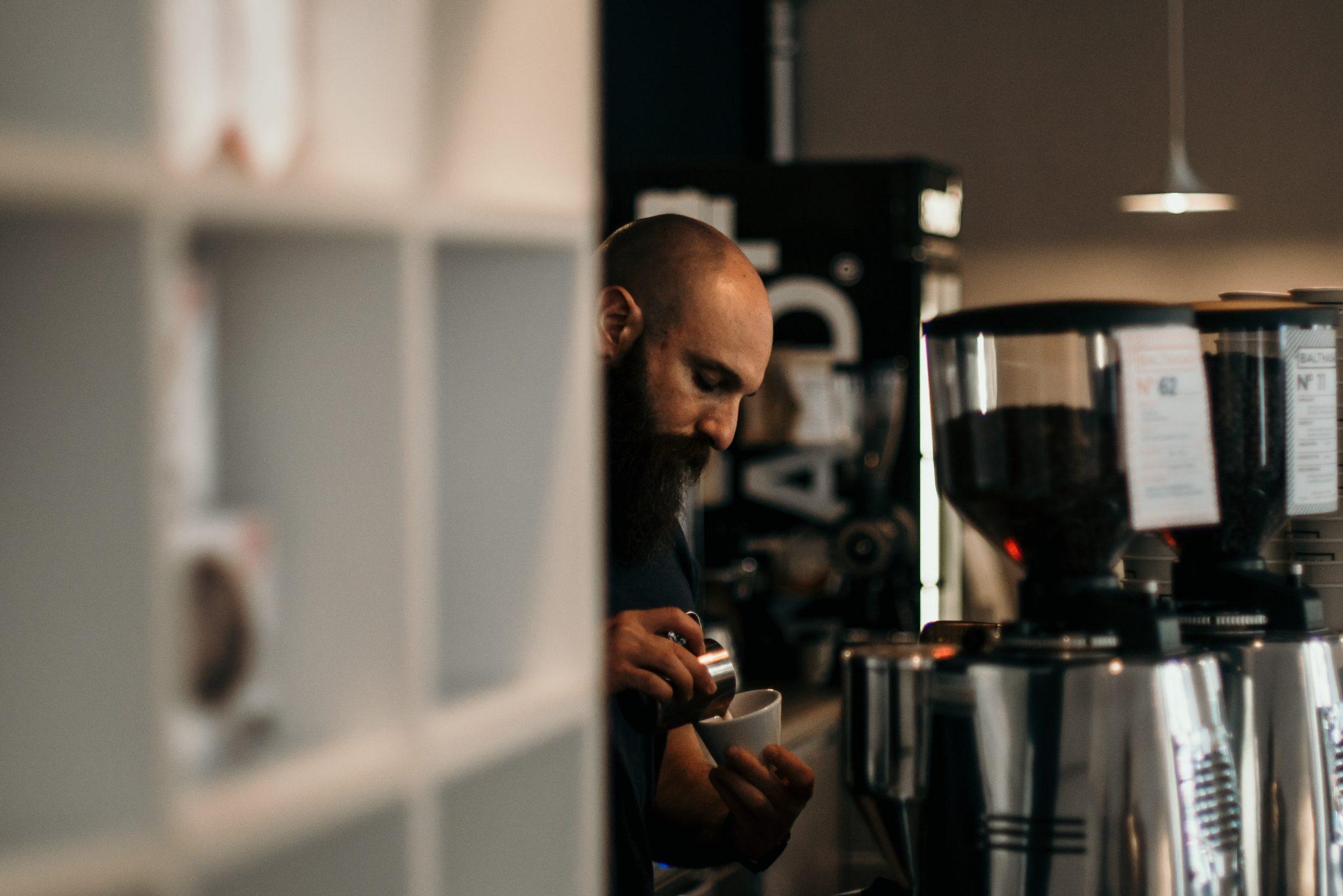Um barista verte o leite dentro da  xícara.