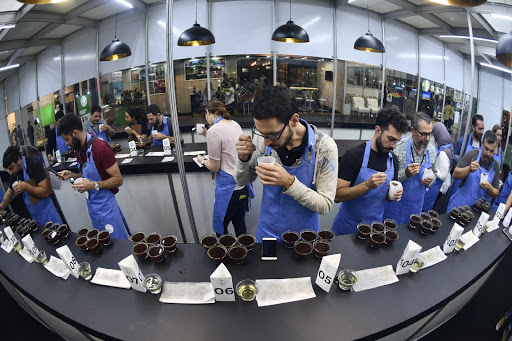 people cupping samples of coffee the year