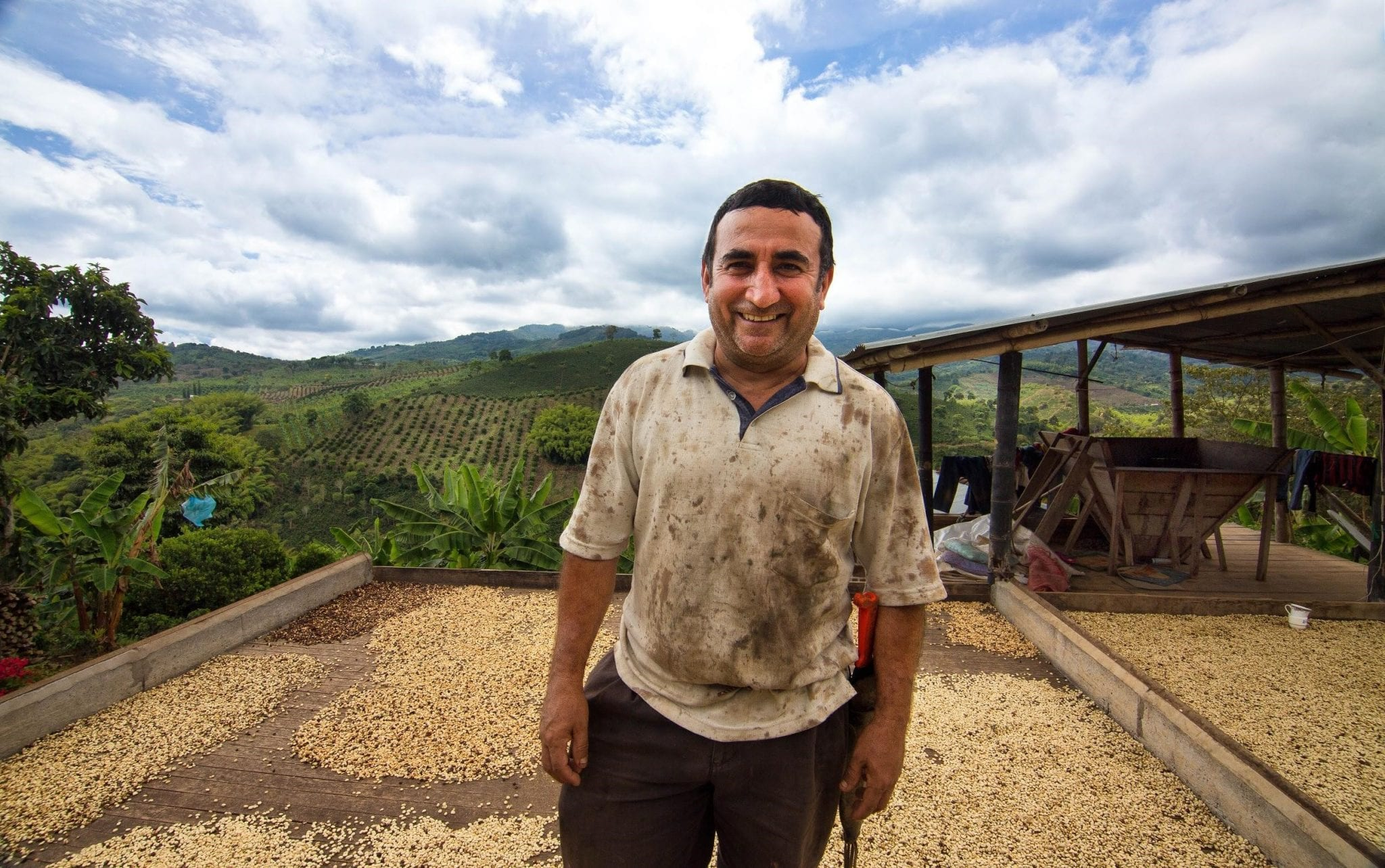 coffee producer smiles for the camara in his farm
