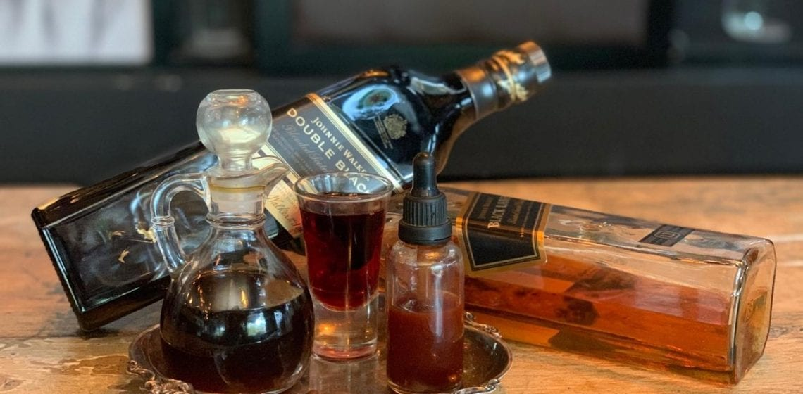 Two bottles of Scotch with glasses of coffee on a silve tray on table