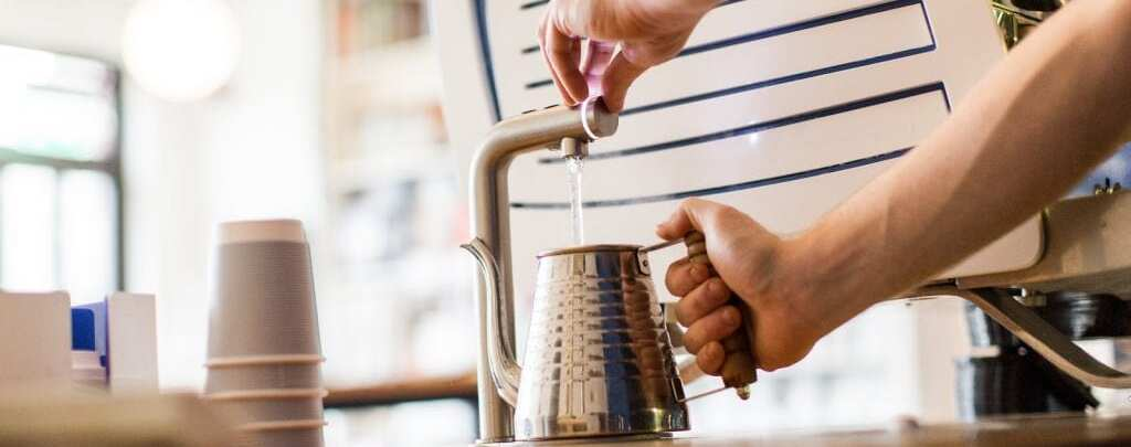 Barista pouring water in a kettle to heat it up