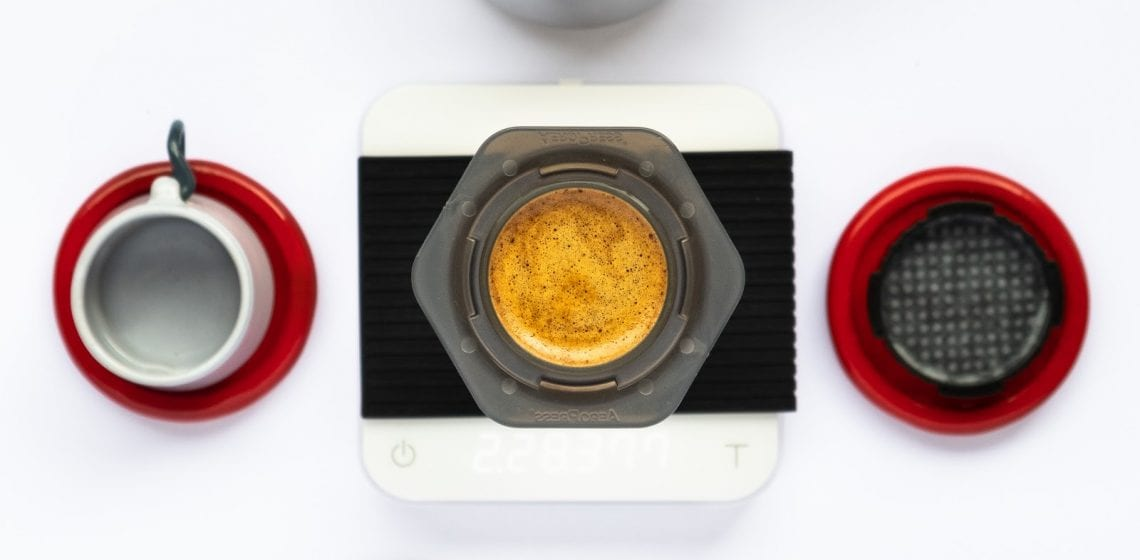 Coffee brewing in a aeropress above a white balance