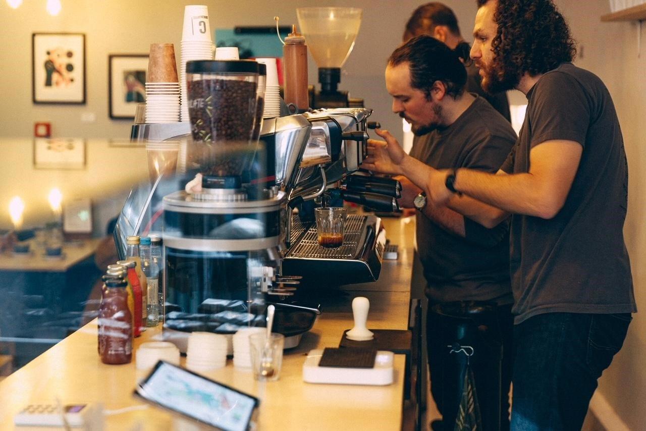 baristas detras de la barra de cafe