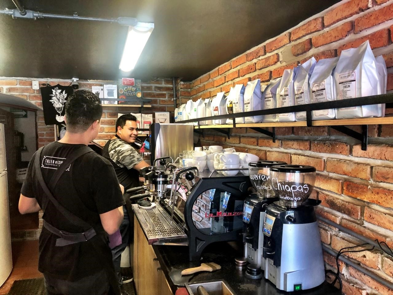 two baristas making coffee for customers