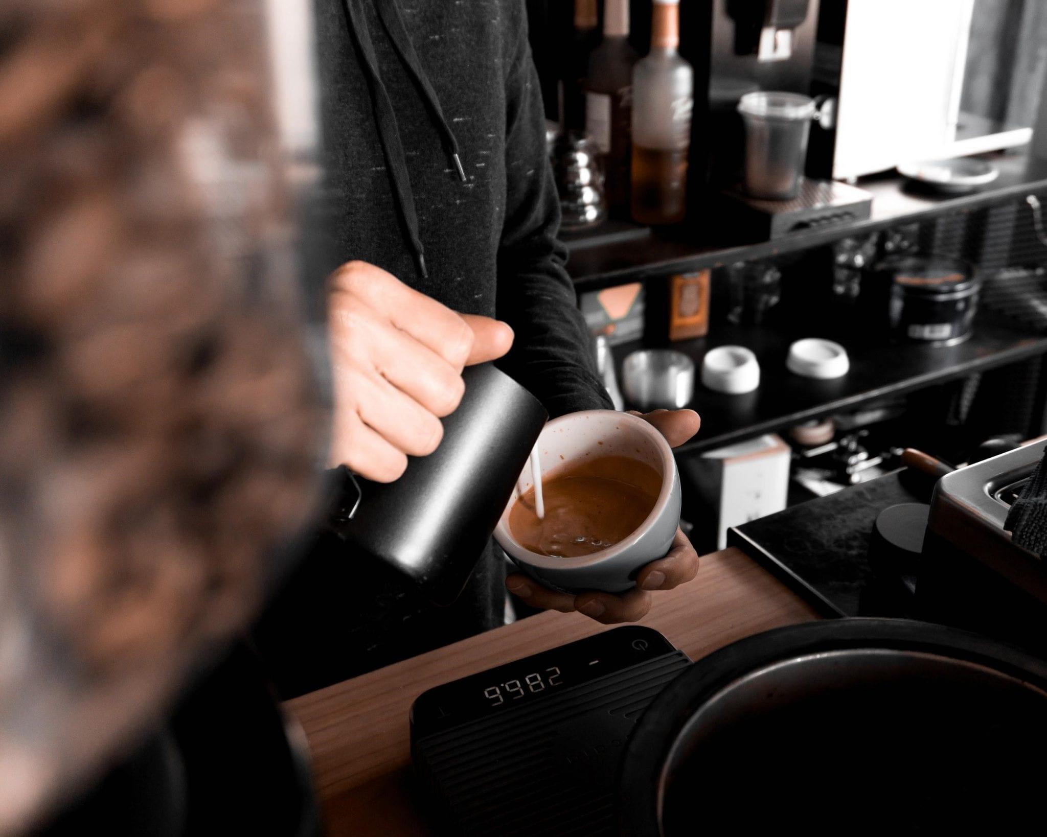 barista preparando un cafe con leche cremada