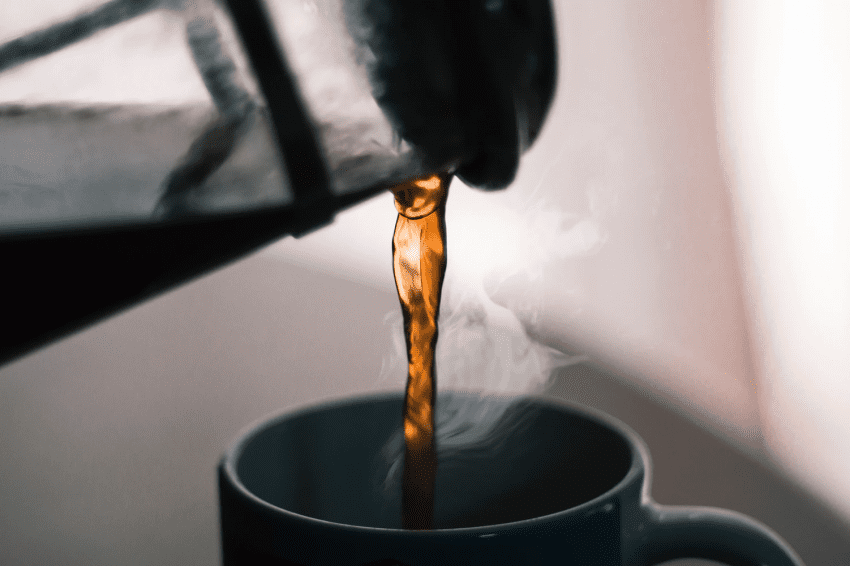 pouring coffee on a cup from a french press
