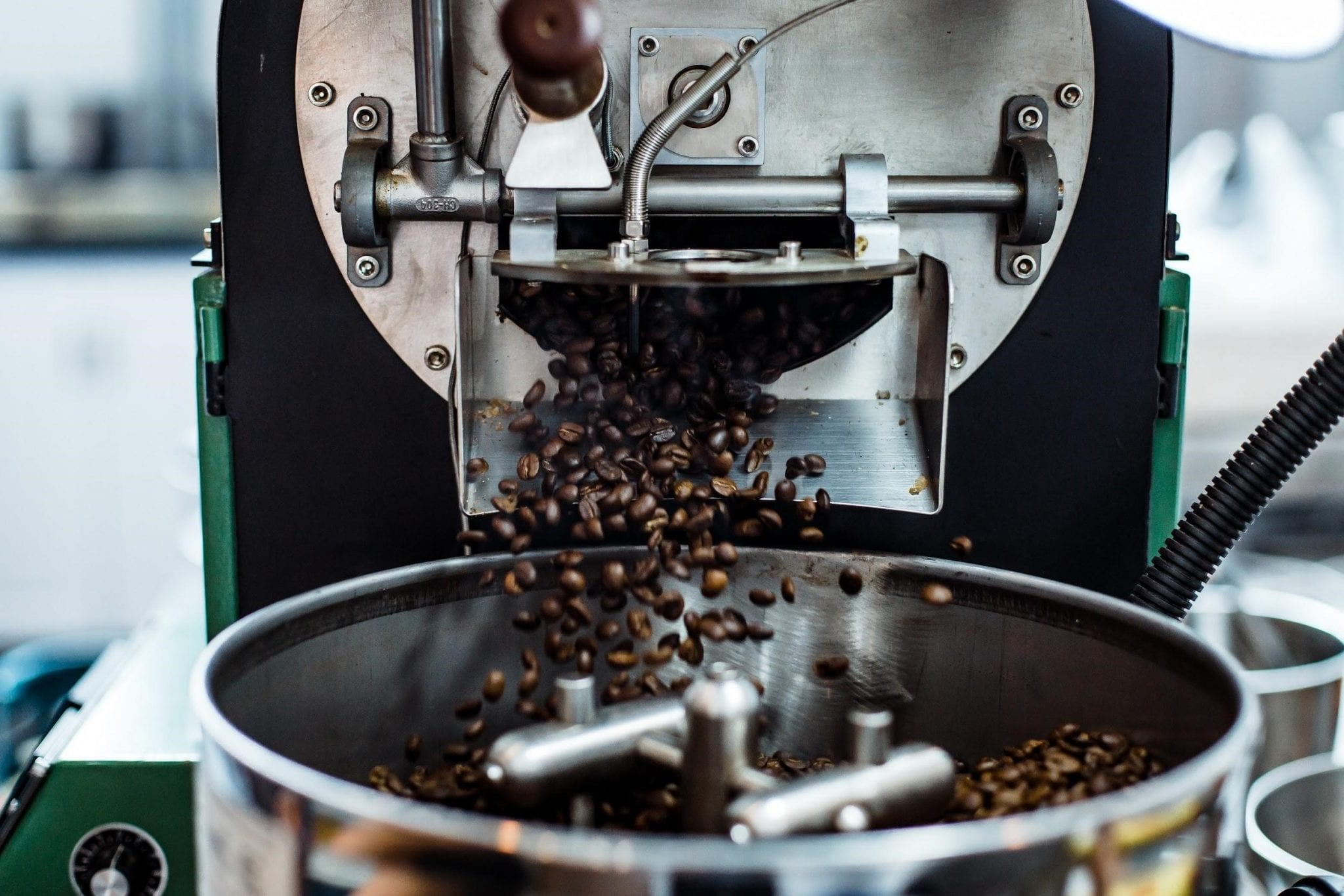 Roasted coffee beans falling into the cooling tray