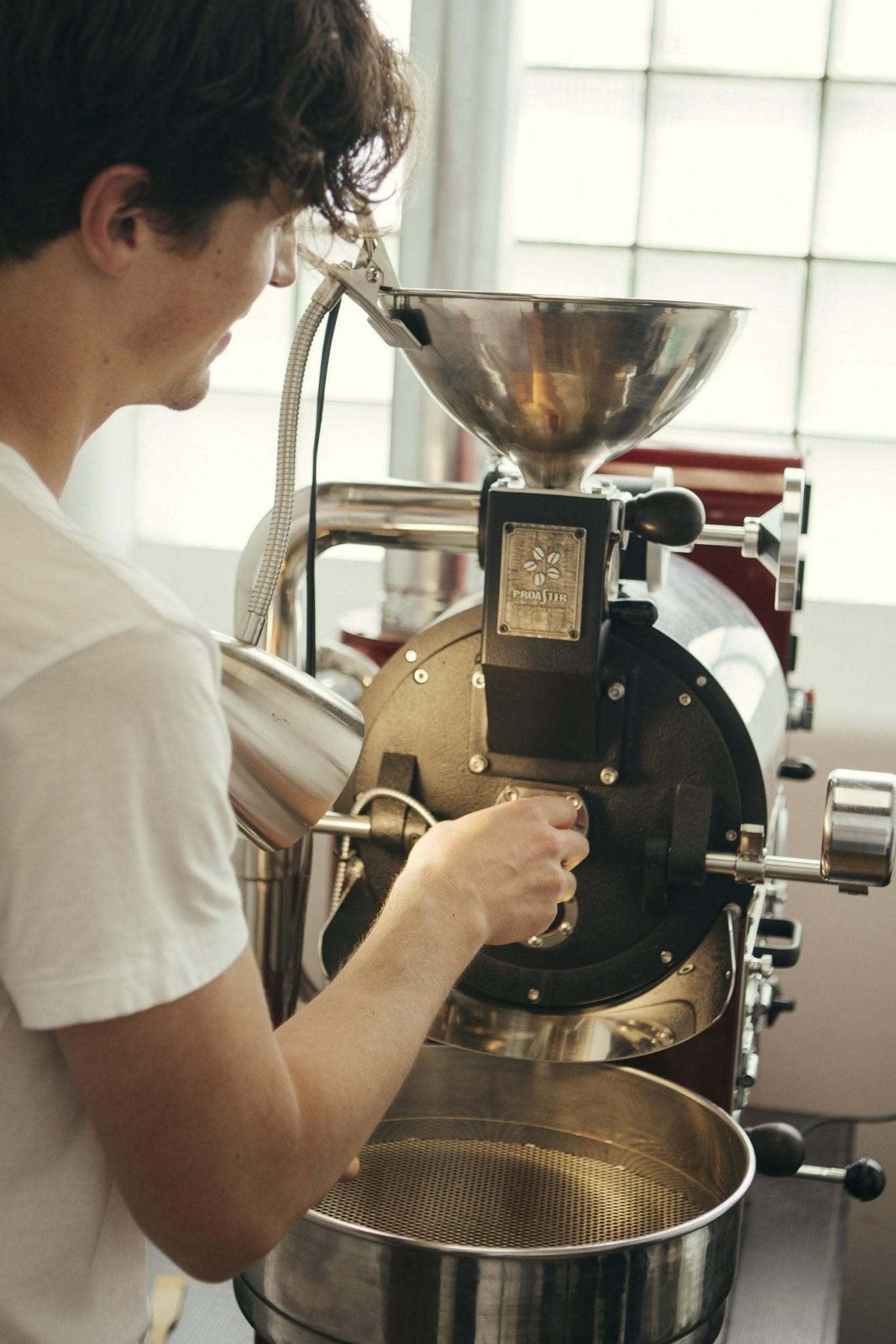 a coffee roaster prepares his next batch of roasted coffee