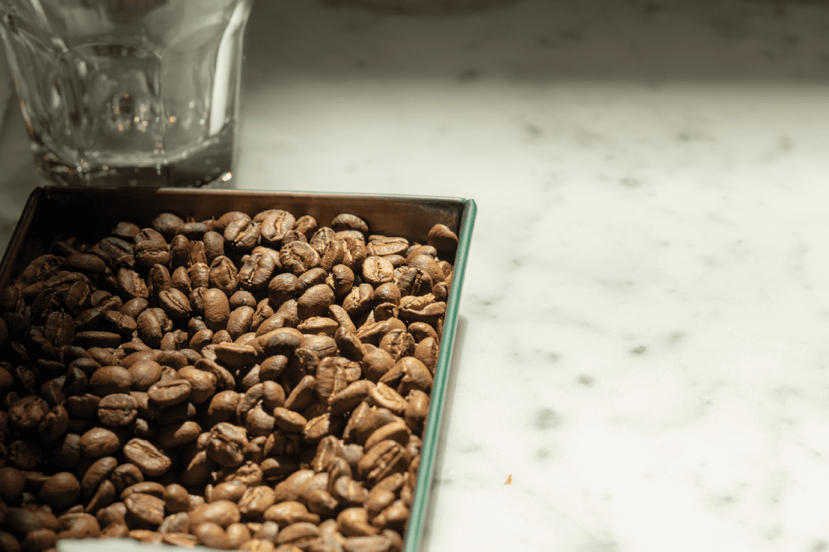 Sample of roasted coffee beans in a marbeled surface