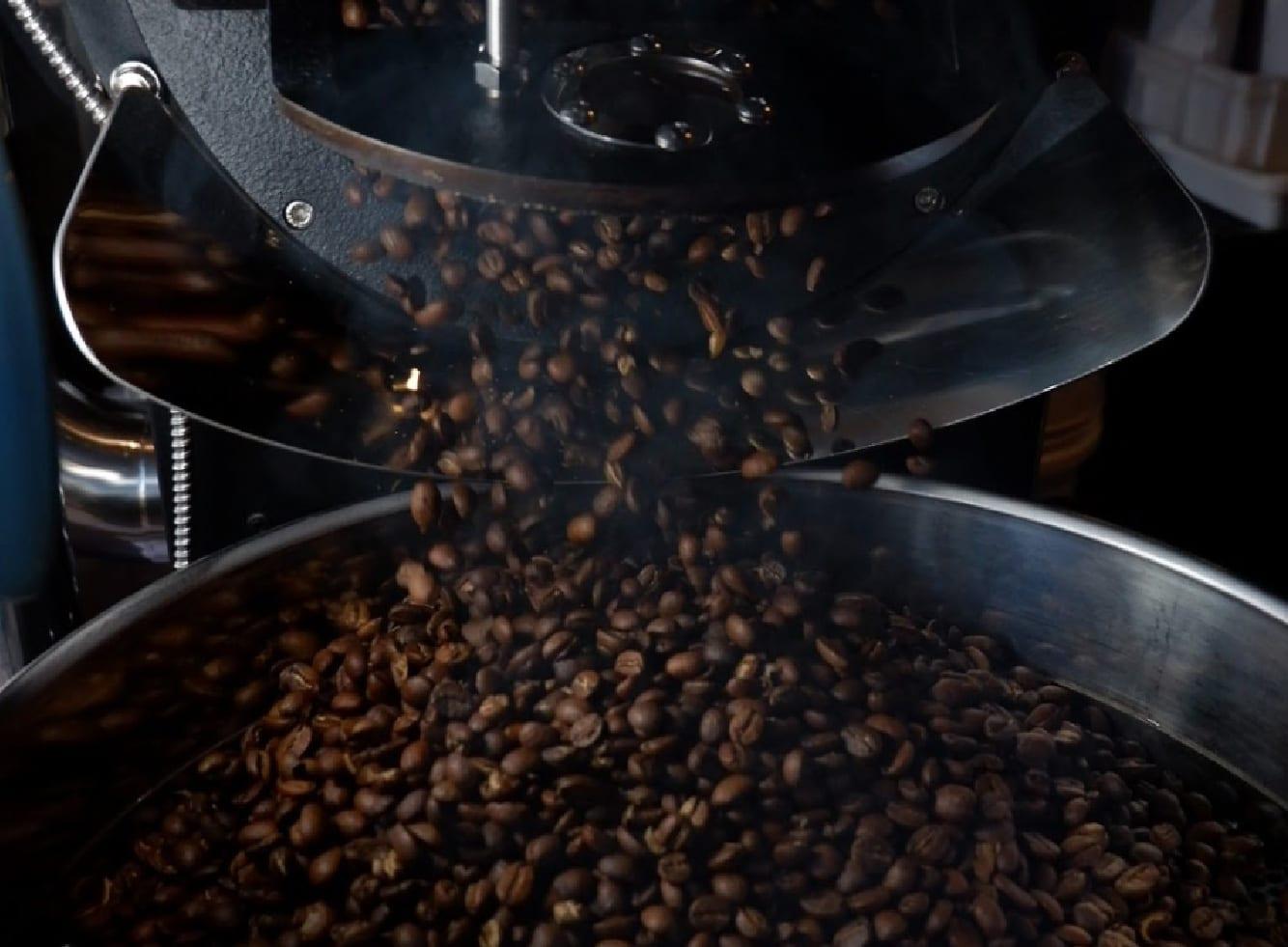 Café recém torrado derramado no resfriador.