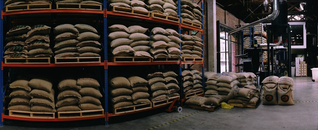 Depot of jute bags with green coffee beans