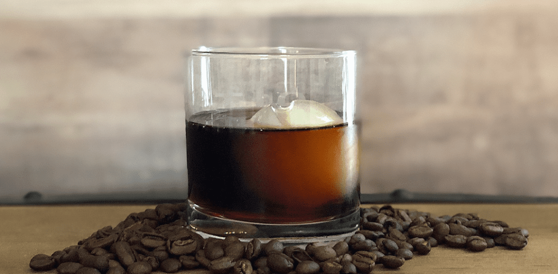 A glass of Pura Vita coffee cocktail on a wooden surface with roasted coffee beans