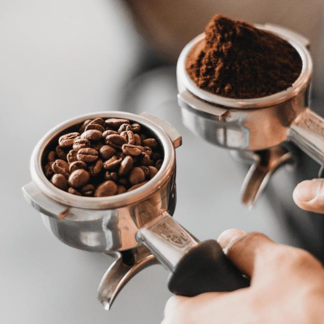 Grãos de café e café moído em porta-filtros.