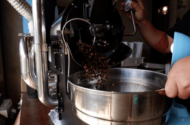 Café torrado cai na bandeja de resfriamento.