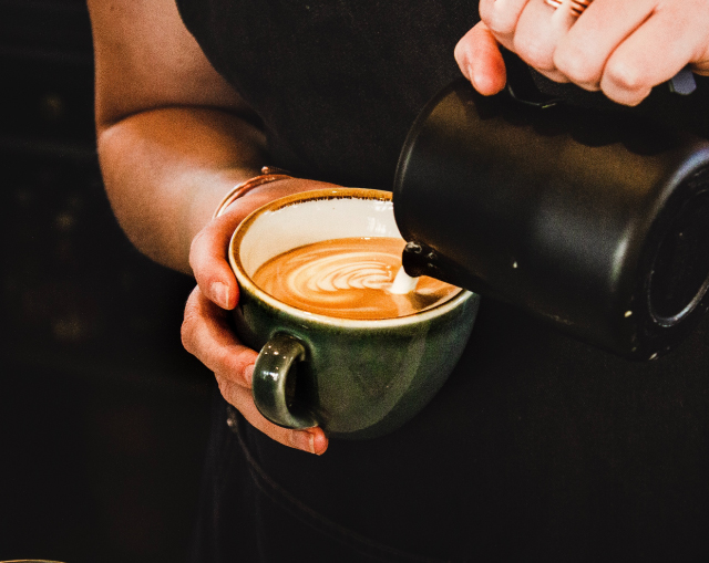 Barista virtiendo latte art