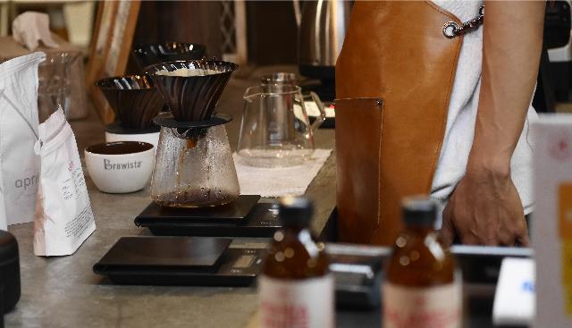 un barista prepara un café usando el método v60