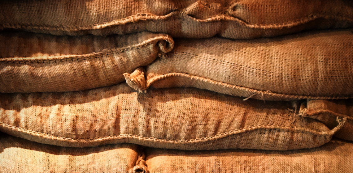 Pile of jute bags with green coffee beans