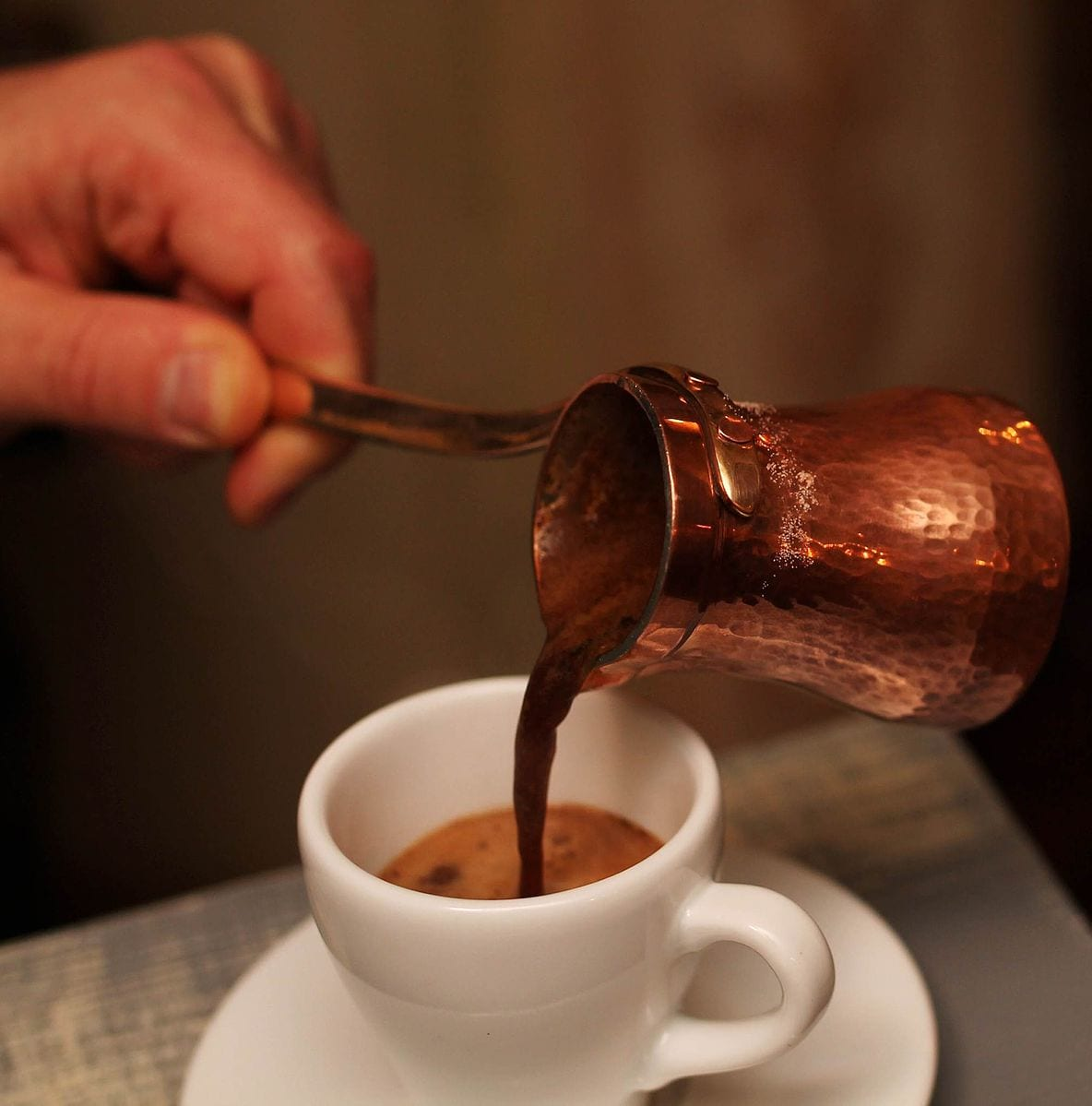 pouring turkish coffee into espresso cup