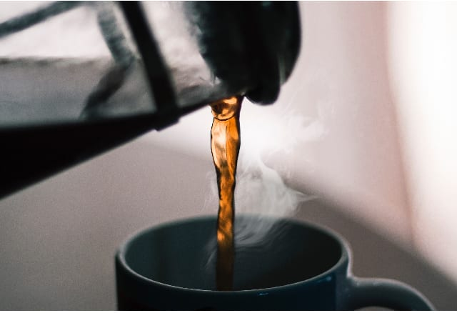 Coffee brewed in a French Press being poured into a cup.
