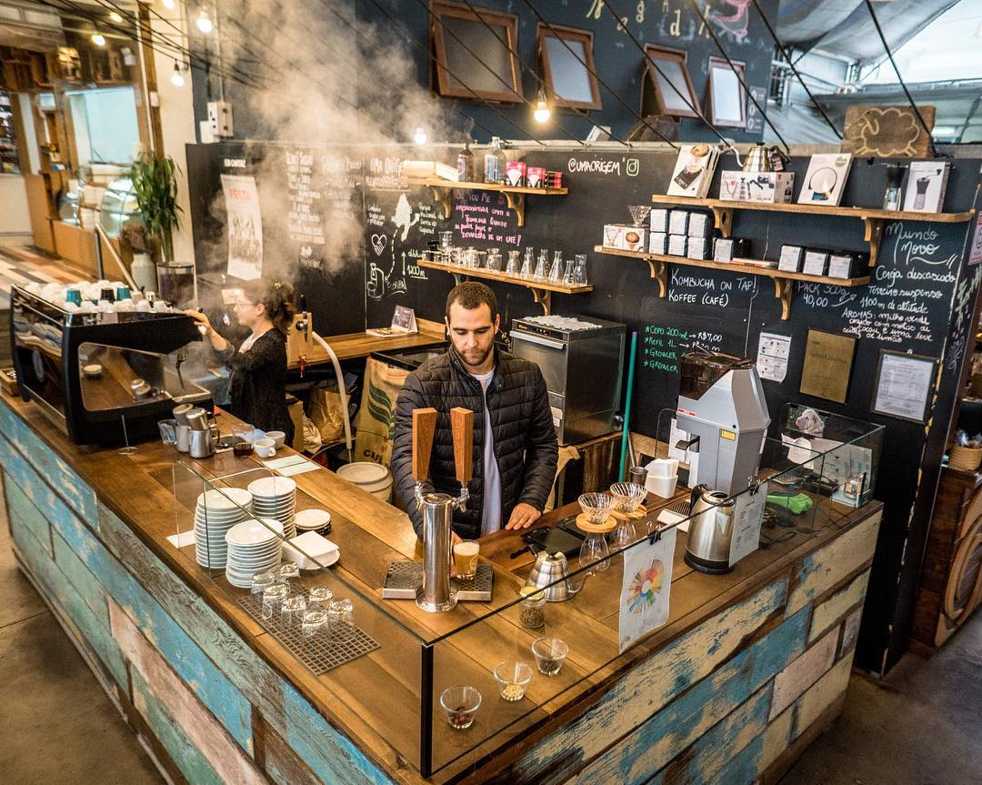 barista behind counter of trendy coffee shop