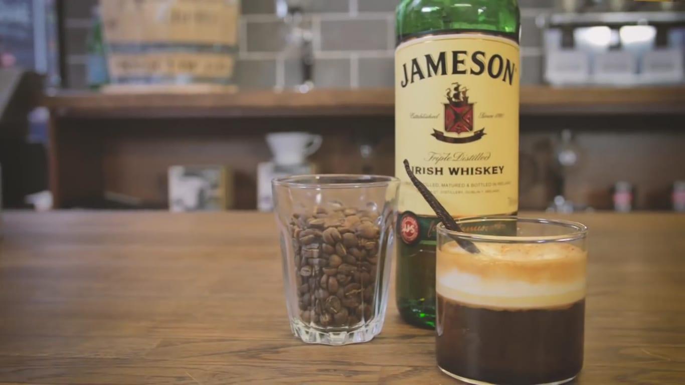 Irish coffee next to Jameson Irish whiskey and coffee beans