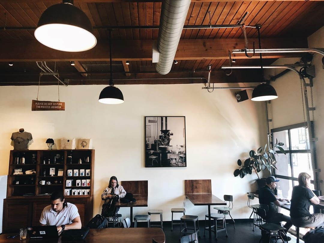 clientes toman cafe mientras leen