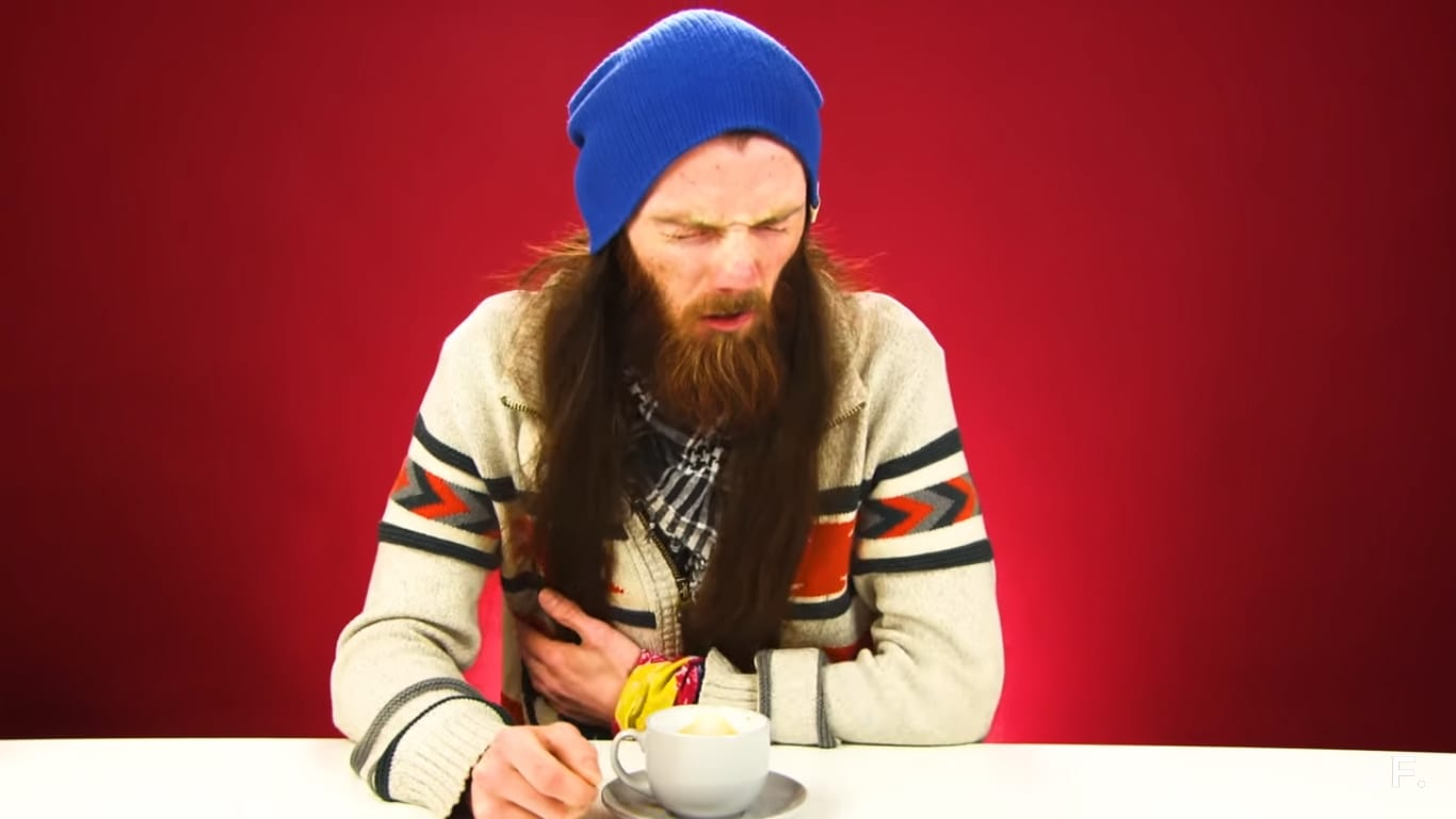 man drinks coffee and looks disgusted