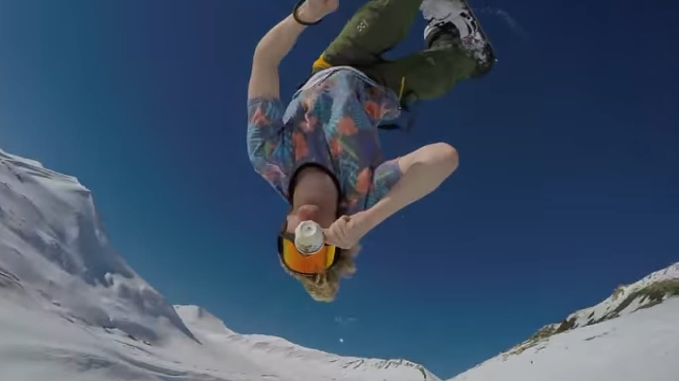Snowboarder drinking coffee during backflip