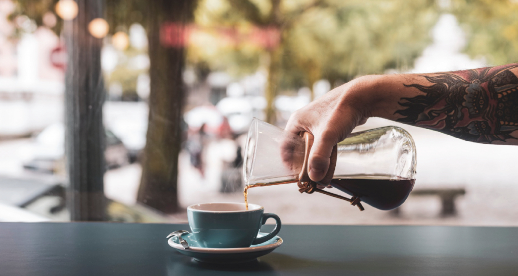 Barista serving coffee from a chemex into a blue cup on a black surface