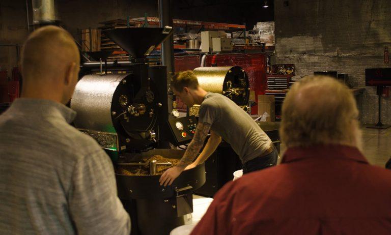 Um torrador inspeciona um lote em resfriamento.